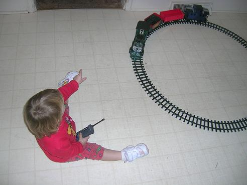 [Here I am playing with my train set that Santa brought me.]