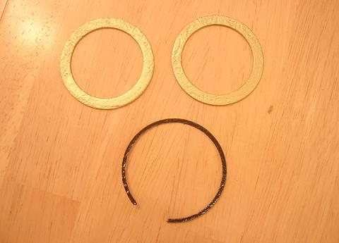 [The two fork washers and one of the retaining rings after being cleaned of all rust and repainted.]