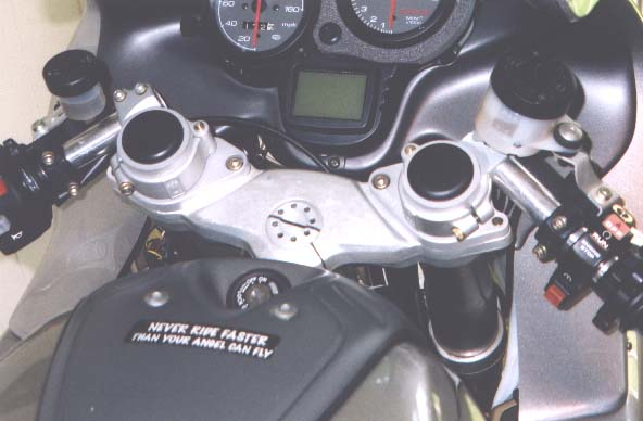 [Picture of the Helibar adapters with Ducati SBK clip-ons to lower the bars.]