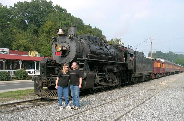 [Vicki and I are posing in front of the train in Bryson City.]